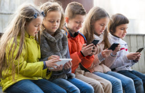 Ordinary kids sitting with mobile devices