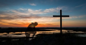 30543-kneelingatcross-cross-sunset-beach-mankneeling.1200w.tn_-860x450_c